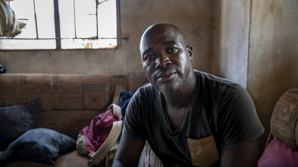 Antonio, 44, sits in the living room of his home in Buzi, damaged by Cyclone Idai.