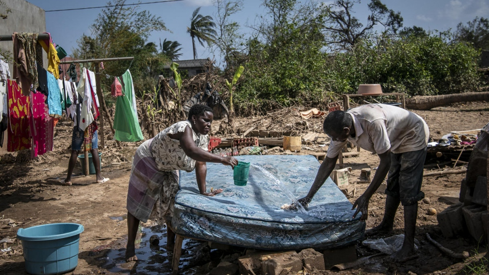 A husband and wife try to salvage their mattress, washing it in the sun in the aftermath of Cyclone Idai, Buzi, Mozambique.