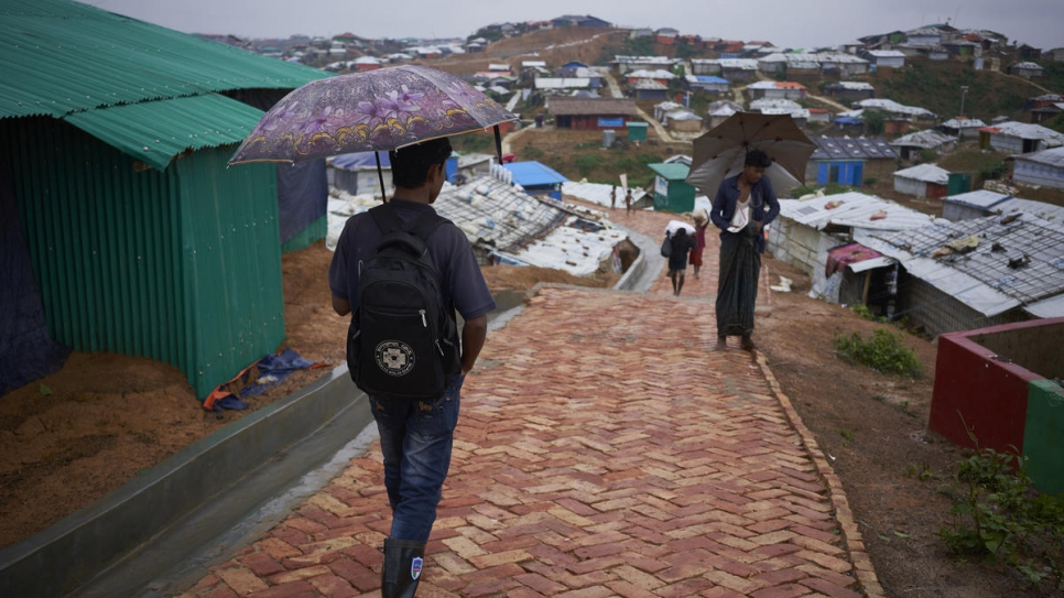 Community health worker and Rohingya refugee Shokat Ali, 26, left, walks down a paved footpath in Camp 4, Kutupalong Expansion Site for Rohingya refugees, Ukhia, Cox's Bazar District, Bangladesh.