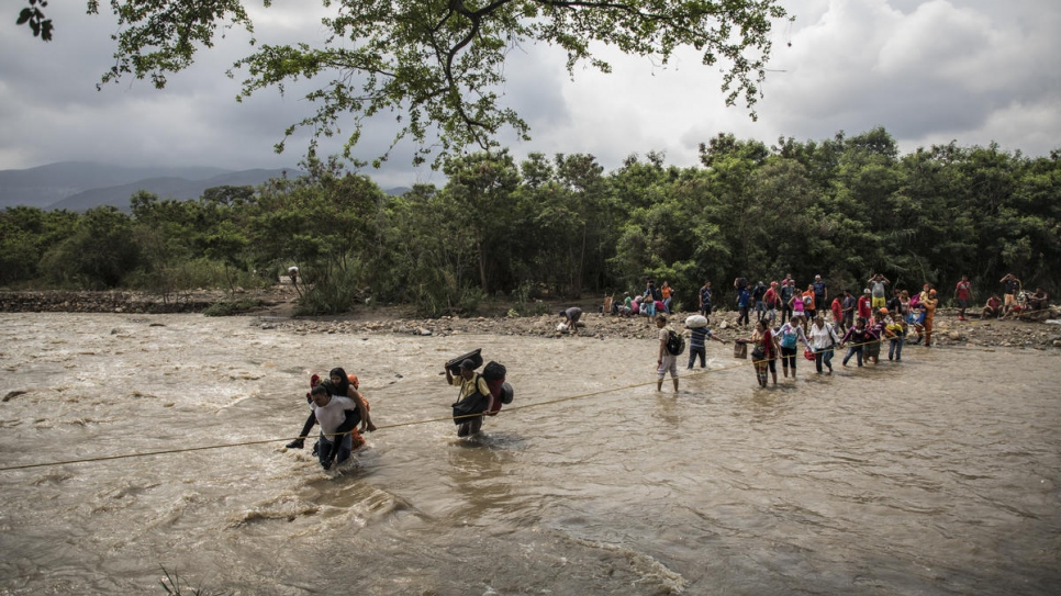 Venezuelan refugees and migrants use a rope to guide themselves across the rain-swollen Tachira River to reach Cúcuta, Colombia.