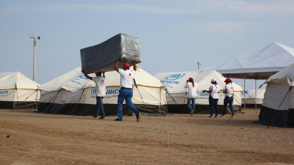 Volunteers from local institutions and NGOs bring mattresses to the new reception centre in Maicao, Colombia.