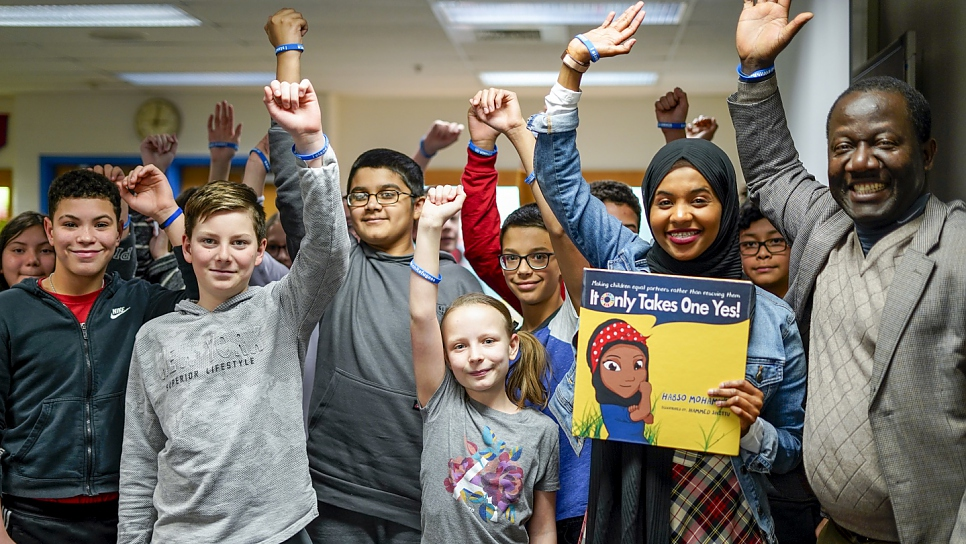Children's book author and former Somali refugee Habso Mohamud poses with students after a book reading at a middle school in the Washington, DC area.