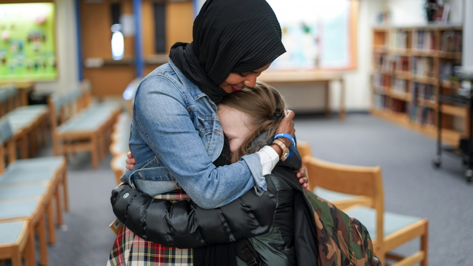 "A young fan embraces former Somali refugee and children's book author Habso Mohamud after a reading of her book ""It Only Takes One Yes."""