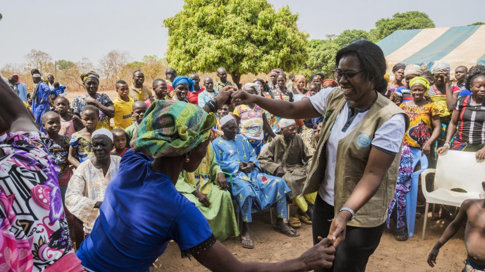 Rosine Zouassi, of the Côte d'Ivoire Women's Legal Aid Association, dances with a village resident at the end of a documentation outreach meeting in Olleo, Côte d'Ivoire.