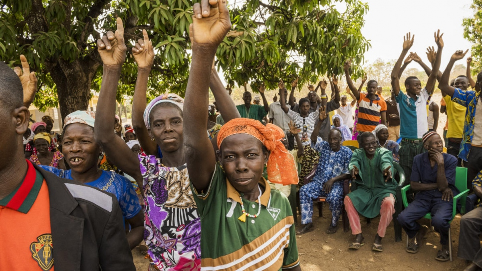 When asked to identify themselves if they are undocumented, village residents in Olleo, Côte d'Ivoire, raise their arms.