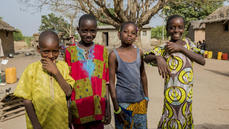 Abdul, Boukary Aisha, and Adiba (left to right) pose for a picture in Kong, Côte d'Ivoire. They are the first generation of the extended Tall family to go to school.
