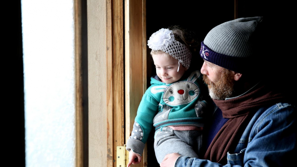 Jihad holds his two-year-old daughter, Habiba, in their recently-rehabilitated house in Homs. New doors and windows were provided by a local NGO with support from UNHCR.