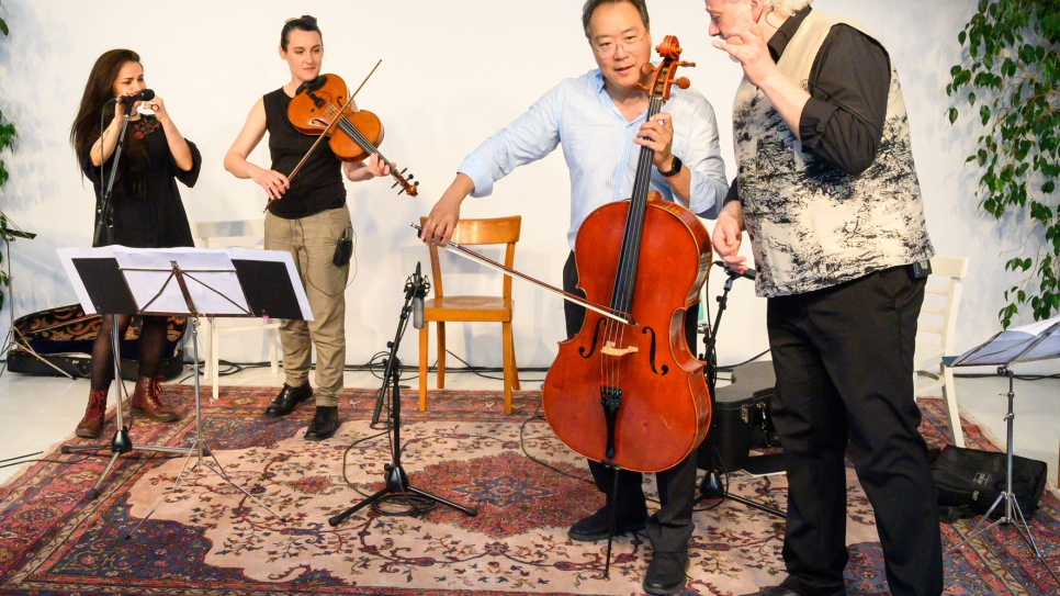 Cellist Yo-Yo Ma plays with refugees at a music workshop in Vienna.