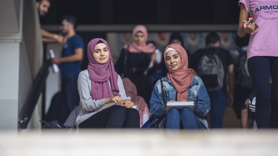 "Weam (left), 19 years old; student in Computer Science (first year) at Lebanese University (UL), on a DAFI scholarship; from Dara'a, Syria; in Lebanon since 2015; interviewed on 03 October 2018 on UL Hadath Campus in Beirut.   On the right is Weam's friend, Diala, a first-ydear Biology student, also on a DAFI scholarship.  Weam: ""We came to Lebanon in the summer of 2015. I entered my final year of high-school here in Lebanon but the classes were in English, which was a very big challenge. I learned mostly online, by myself. I also had to face some degree of exclusion then as I was the only Syrian student.   During my first year at university, I took Physics, but then I changed to Computer Science. I have just started actually.  My parents, my two brothers and my sister live in Batroun, north of Beirut. I live here by myself, in a student dorm. I am the oldest one. My mother is a nurse and my father is a religious teacher.   I feel very happy to be given the chance to study at university, as it is the road towards independence.   Life on campus is both beautiful and tiring at the same time. I get to meet a lot of new people. Since I have started my college studies, I have become stronger, in terms of my personality as well as in the area of decision-making.   At the moment I am learning English, French, Greek and Turkish.   On the weekends, I like to play football and tennis, and to walk in the forest. I also love video games. My professional goal is to work in the field of programming or gaming, as a manager. But it will not be easy: first, I will need to financial means to do so and secondly, there are not too many gaming companies in the region. That means I will probably have to go abroad to pursue my career goals.   My message to everyone listening is that one has to put in a lot of willpower and hard work to achieve one's dreams."""