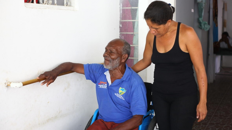A Venezuelan woman supports a Colombian man in a wheelchair at Grandpa's House in Riohacha, Colombia.
