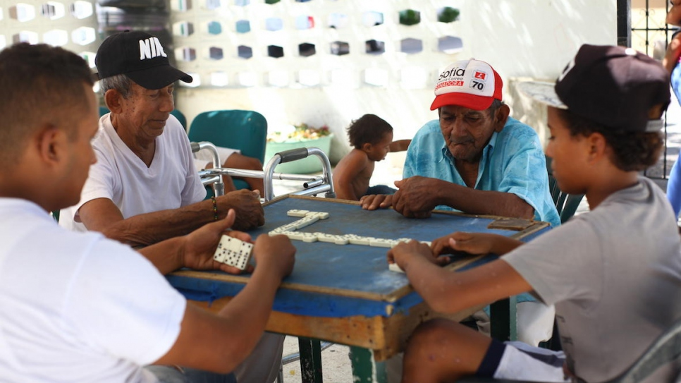 Older Colombians and young Venezuelans play dominoes Grandpa's House in Riohacha, northern Colombia.