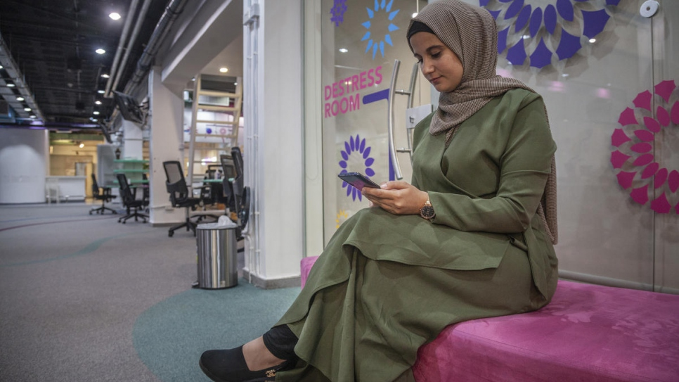 Amani checks her phone at Zain Innovation Campus in Amman, where she and her business partner Ehab often meet and work.