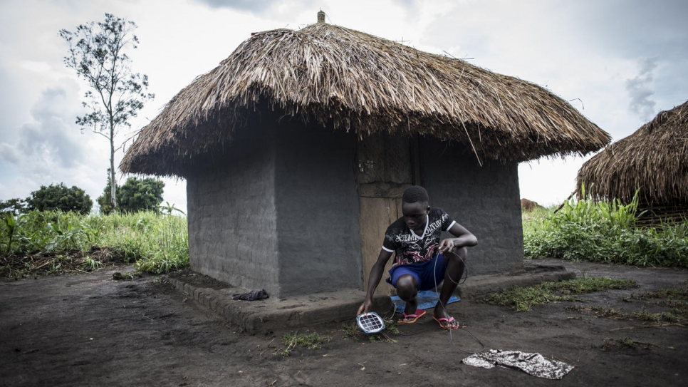 South Sudanese refugee Gift, 14, places charge his self-made solar lamp so he can study at night. Gifted attends school in the Biringi Refugee Settlement in the Democratic Republic of the Congo.