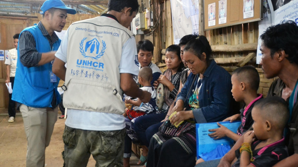 Refugee families from Myanmar are briefed by UNHCR staff before departing Mae La temporary shelter in Tha Song Yang district, Tak province, western Thailand.