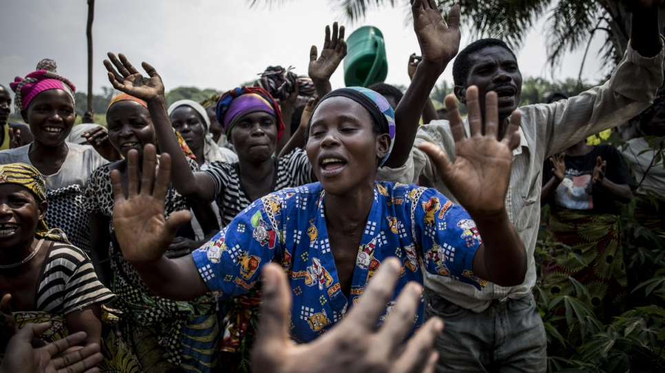 Claudine Nyanzira, a 29-year-old Burundian refugee who is six months pregnant and a beneficiary of Evariste Mfaume's agricultural project, sings and dances at Lusenda refugee camp.