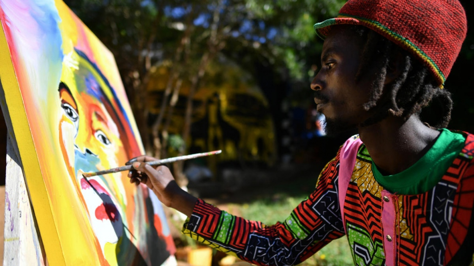 Mike, who fled Burundi in 2015, works on a painting at the art centre.