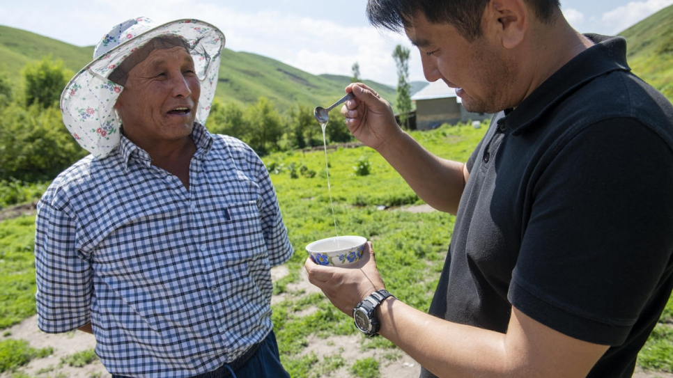 Tasting his honey with lawyer Azizbek Ashurov, who helped him to gain citizenship.