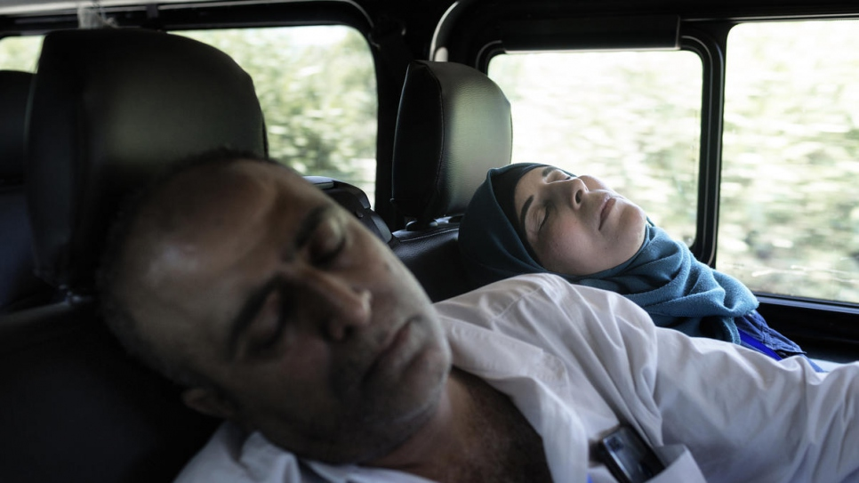 Ammar Issa, 48, and his wife Hanadi, 39, Palestinian refugees from Syria, sleep during the drive from Fiumicino Airport to their new home in Rome.