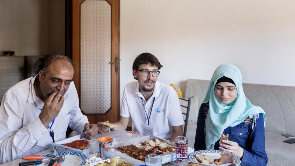 Simone Scotta (centre), of the Italian Federation of Evangelical Churches, eats pizza with Ammar Issa, 48, and Sara, 16, Palestinian refugees from Syria newly arrived in Rome from Lebanon.
