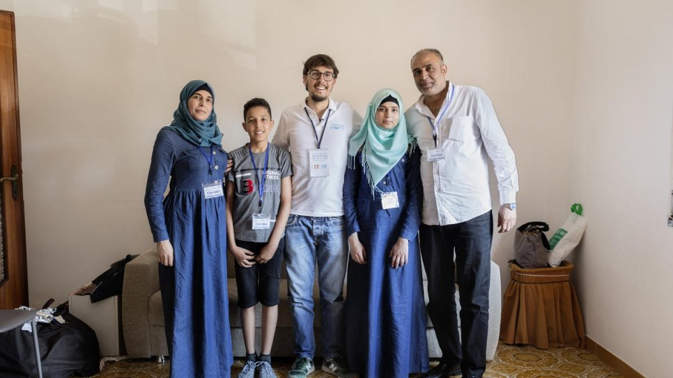 Simone Scotta of the Federation of Evangelical Churches, (centre), stands with a Palestinian refugee family from Syria (left to right) Hanadi, 39, Yasser Arafat, 13, Sara, 16 and Ammar Issa, 48.