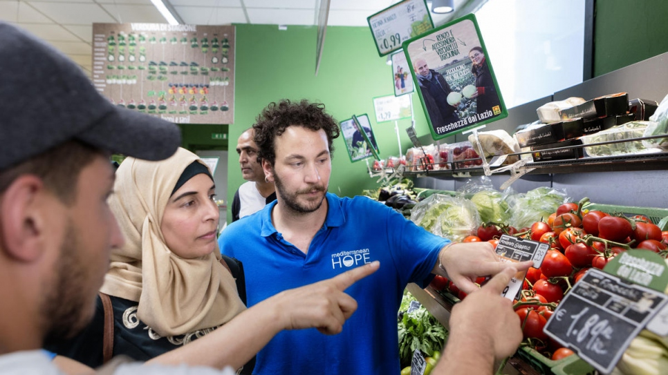 Stefano Specchia from the Federation of Evangelical Churches shows Hanadi, 39 and a Palestinian refugee from Syria, how Italian supermarkets label vegetables.