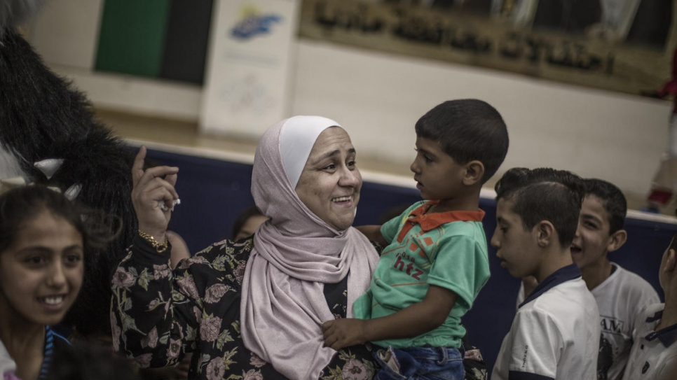 Abeer Khreisha plays with a Syrian refugee child at a community centre in Madaba, Jordan.