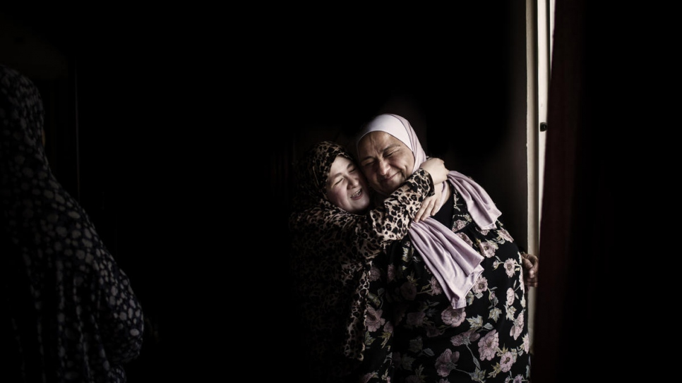 The daughter of Syrian refugee Haifaa Al Dallal hugs Abeer Khreisha as she visits their home in Madaba, Jordan