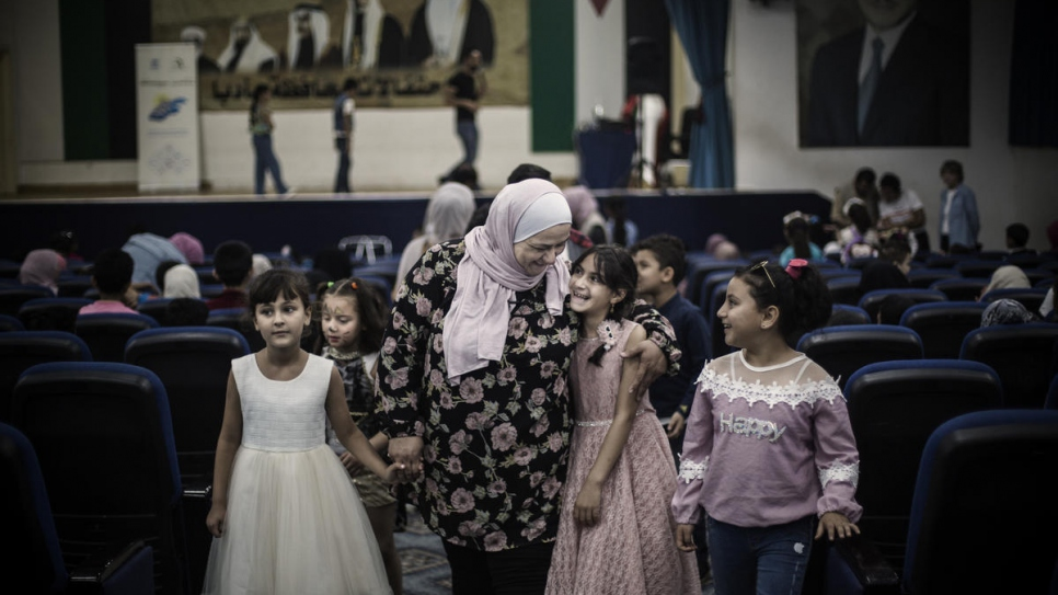 Abeer Khreisha is surrounded by young Syrian refugees during an event at a community centre in Madaba, Jordan.