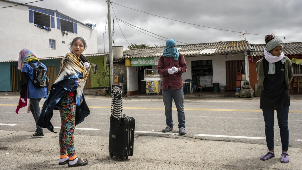 Venezuelan migrants and refugees put on warm clothes in La Laguna village before  continuing their journey through the mountain road and reach the Berlin pass which is over 3000 metres high.