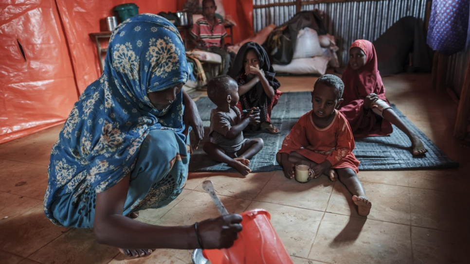 A Somali refugee woman feeds her children at a World Vision's school used as a temporary shelter in Bur Amino, Ethiopia.