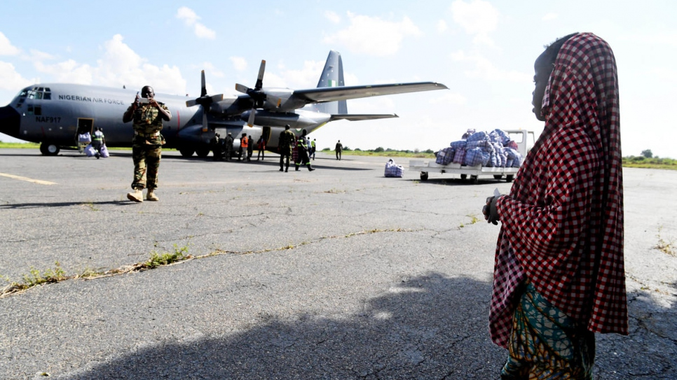 A young Nigerian refugee looks on as the plane that will take her and her family back to Nigeria waits on the runway.