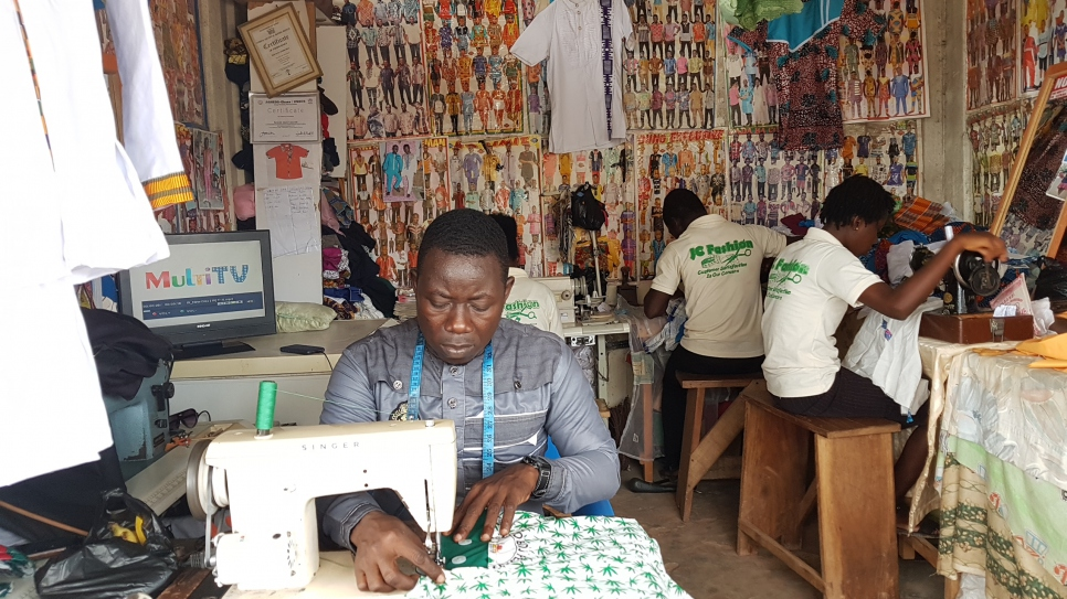 Ivorian refugee and fashion designer Bouhe Jean Claude works at his sewing machine in his tailoring shop in central Ghana.
