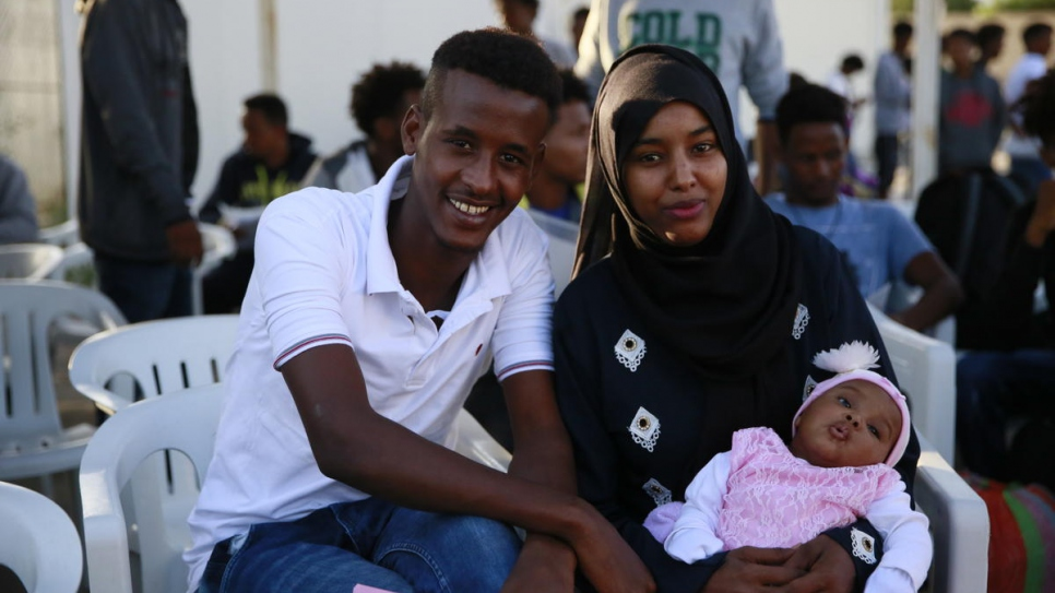 Somali parents Abdulbasit and Zainab sit with their two-month-old daughter at the Gathering and Departure Facility in Tripoli ahead of the evacuation flight to Rwanda.
