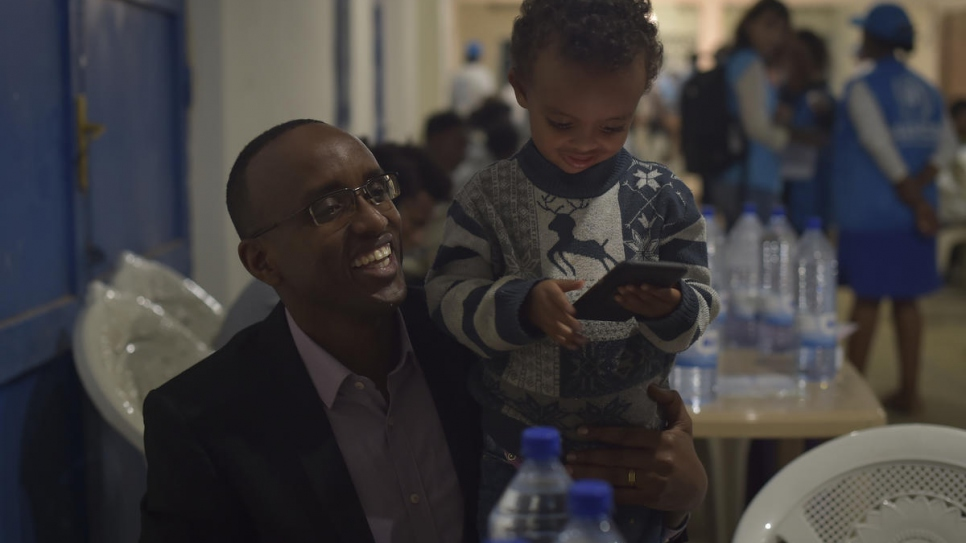 District Mayor Richard Mutabazi plays with a young child at the Gathora Emergency Transit Center, Rwanda.