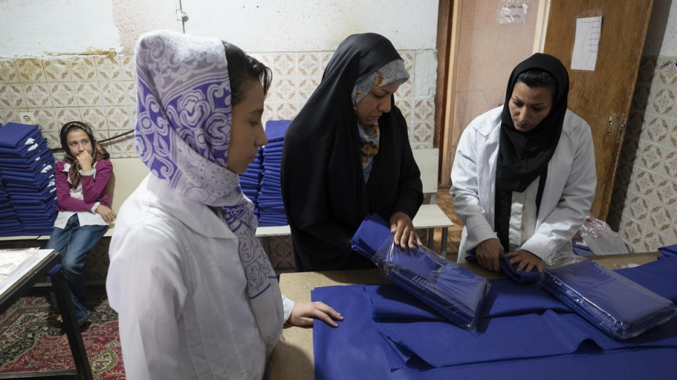 Zeynab (centre) supervises fellow Afghan refugees at her tailoring workshop in Shiraz.