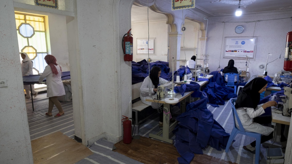 Iranian and Afghan employees work at the tailoring workshop.