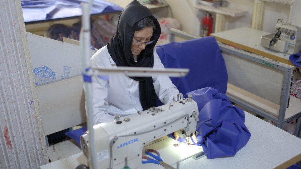 Afghan refugee Mahroo, 40, makes hospital gowns at the tailoring workshop.