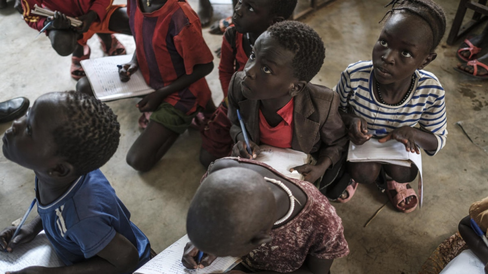 Refugee school children write in notebooks at Jewi Refugee Camp Primary School in Gambella. There are never enough books or teachers to meet the demand for learning.