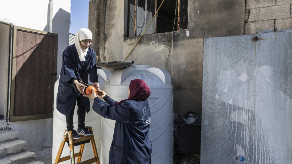 Syrian refugee trainee Buthayna helps Safaa install a water tank in Irbid, Jordan.