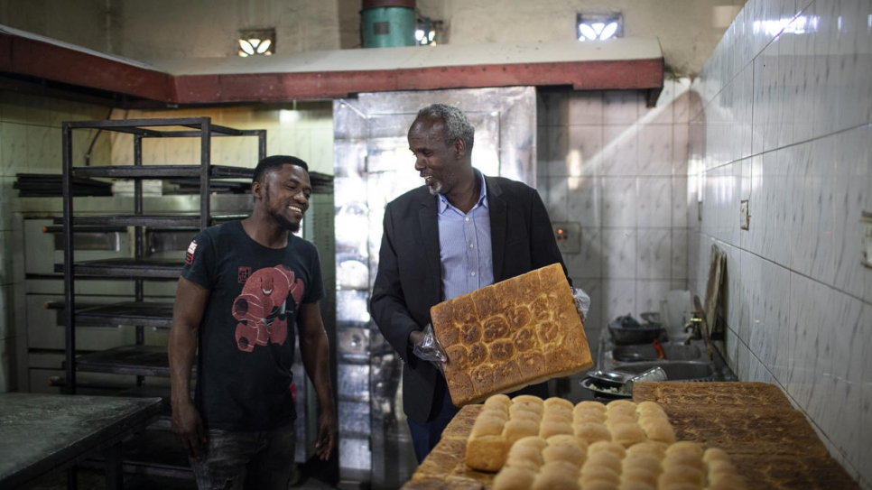 Restaurant owner and Somali refugee Hassan Abdi, right, chats with a Zambian employee at his restaurant in the outskirts of Lusaka, Zambia.