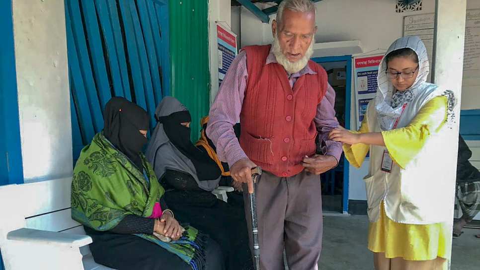 Naushin Anjum (right) guides her patient Abdul Quddus at the UNHCR-funded Physiotherapy and Physical Rehabilitation Centre in Shamlapur, Bangladesh.