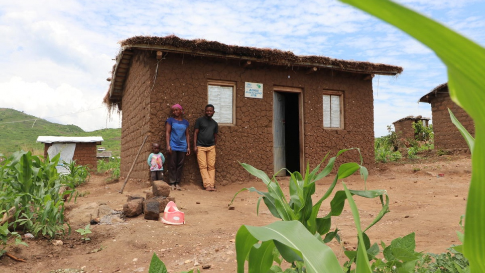 Burundian refugee Aisha, her child and her husband Matias stand outside their house in Mulongwe settlement, Democratic Republic of the Congo.