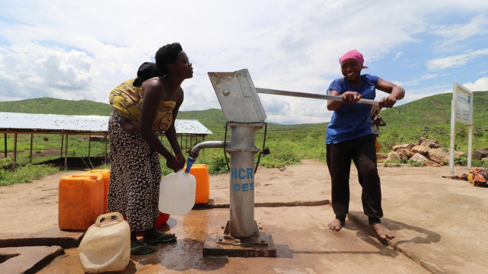 Aisha (right) pumps water from a borehole in Mulongwe settlement, Democratic Republic of the Congo.