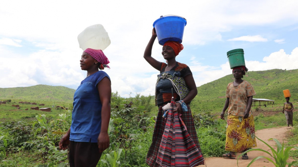 Aisha (front), walks home with other women after fetching water from a borehole in Mulongwe settlement, Democratic Republic of the Congo.