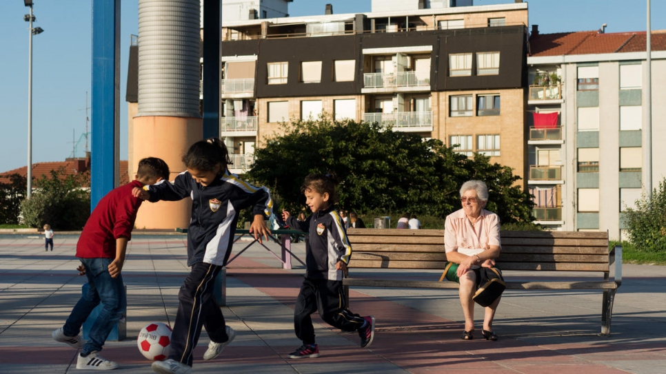 """People say to me, 'What are you doing helping those people?' and I say, 'It is more what they are doing for me!'"" Begoña Herrero, a local volunteer, watches the sponsored family's children as they play football in a park in Portugalete, Spain."