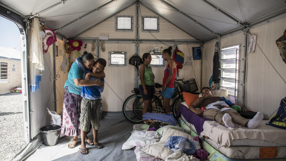 Nelly hugs her grandson Moisés in the family tent in Boa Vista, Brazil, while her daughter, who is sick rests, on the bed.