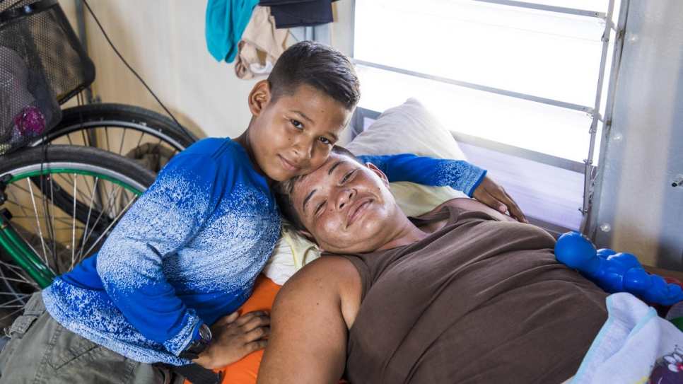 Moisés and his mother in the family tent in Rondon 3 shelter in Boa Vista, Brazil.