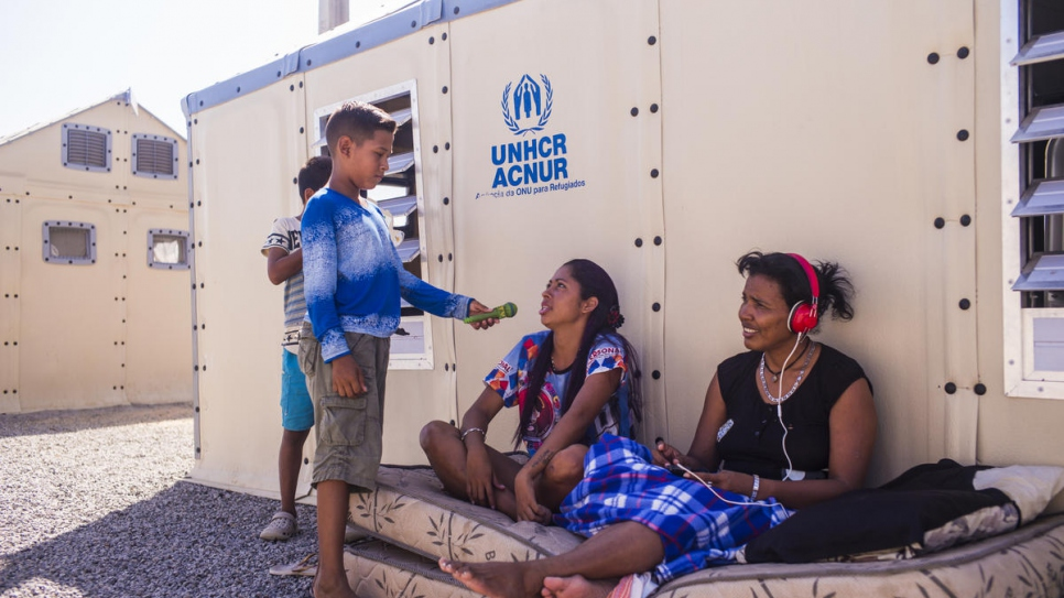 Moisés plays journalist, interviewing refugees in front of their shelter in Rondon 3 refugee camp in Boa Vista, Brazil.