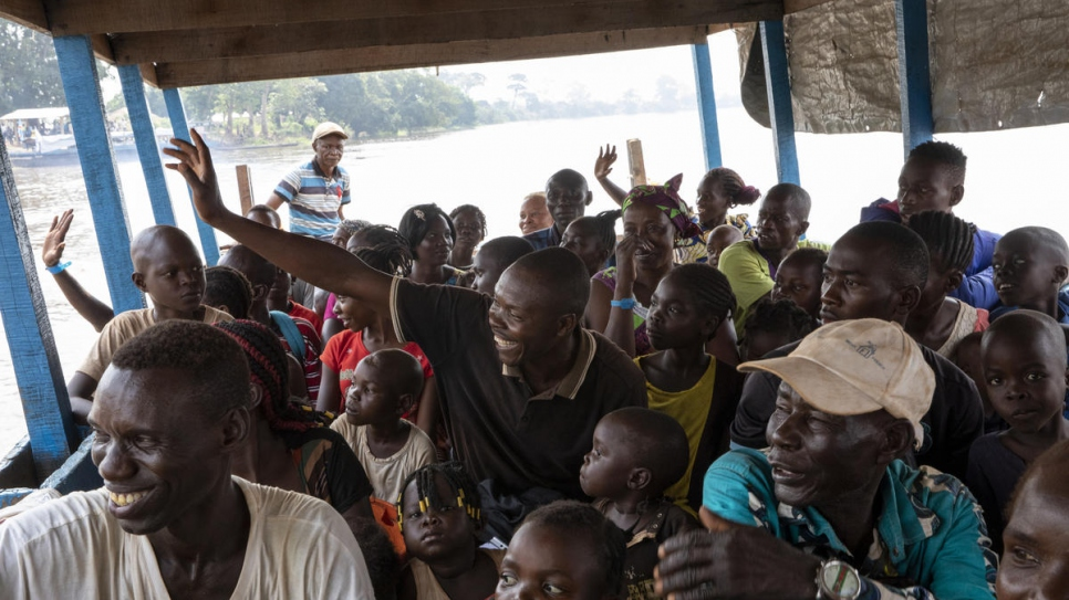 Voluntary returnees wave as the boat carrying them back to the Central African Republic leaves Zongo port in the Democratic Republic of the Congo, 21 November.