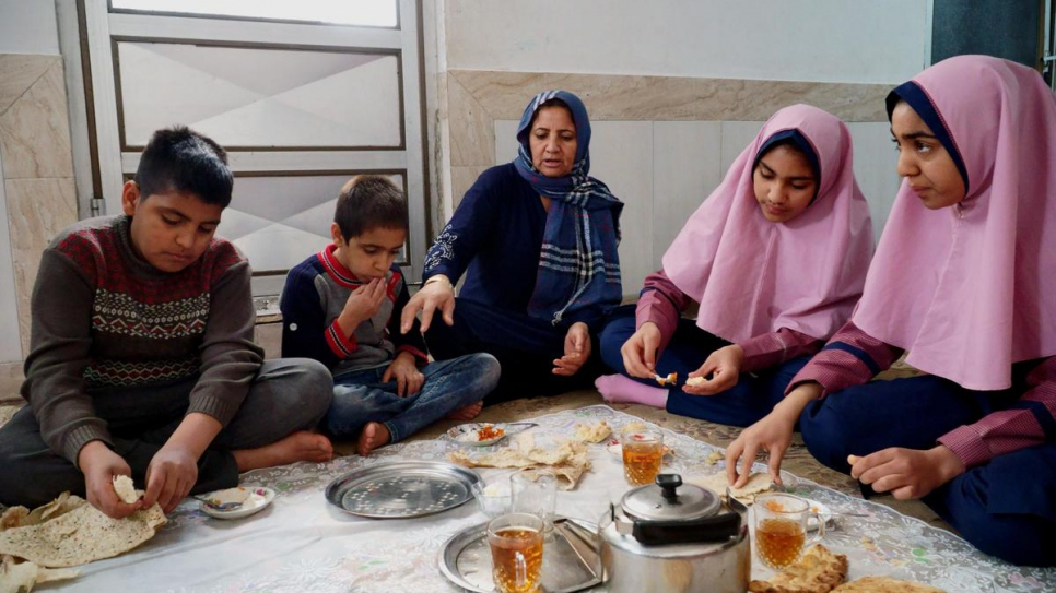 Afghan refugee Halime (centre) prepares breakfast for two of her sons and her daughters Parisa, 16, and Parimah, 14, at home in Esfahan, central Iran.